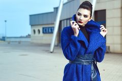 Beautiful model with perfect make up and hair scrapped back into a bun standing on the street in blue coat with leather belt stock image