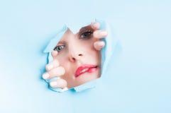 Beautiful model with perfect skin biting lip thru ripped board Stock Photography