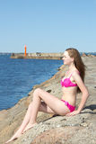 Beautiful model in pink bikini sitting on rocky beach Royalty Free Stock Image