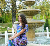 Beautiful model posing next to fountain. Amazing teen model posing near fantastic fountain Royalty Free Stock Image
