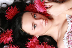 Beautiful model in red flowers Stock Image