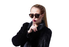 Beautiful model with red lips and blonde hair in black fur coat stock images
