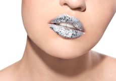 Beautiful model with silver lips makeup on white background. Beautiful young model with silver lips makeup on white background royalty free stock image