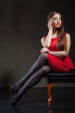 Beautiful model sitting on chair in studio Royalty Free Stock Image