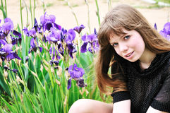 Beautiful model sitting next to flowers Stock Photography