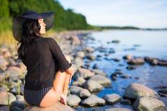 Beautiful model sitting on rocky beach Stock Image