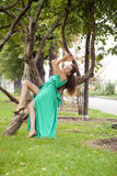 Beautiful model sitting on a tree in a long green dress Royalty Free Stock Images