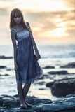 Beautiful model standing on rocks by the sea Stock Photos