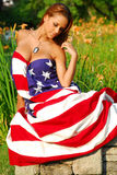 Beautiful model in the Stars and Stripes. Beautiful redheaded model adorned in the Stars and Stripes Stock Photography