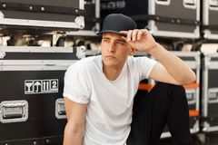 Beautiful model stylish man in a black cap and a white T-shirt