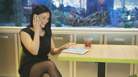 Beautiful model talking on a smartphone indoors. Beautiful brunette model aged 20s sitting at a cafe and talking on a smartphone in the background blue aquarium stock video