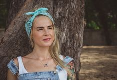 Beautiful model with tattoos sitting on the beach near a tree. Wears a turquoise bandana. A modern woman. Rest in royalty free stock photography