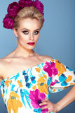 Beautiful model with updo hair and perfect bright make up wearing colorful open shoulder dress with floral print and peony garland Stock Photography