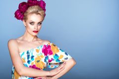 Beautiful model with updo hair and perfect bright make up wearing colorful open shoulder dress with floral print and peony garland Stock Image