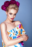 Beautiful model with updo hair and perfect bright make up wearing colorful open shoulder dress with floral print and peony garland Royalty Free Stock Photography