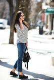 Beautiful model walks with phone Stock Photography