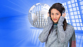 Beautiful model wearing winter clothes listening to music Stock Images