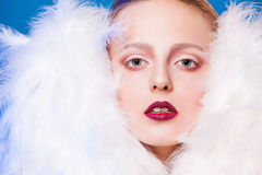 Beautiful model in white cape of feathers with red lips. Fashion photo Stock Photo