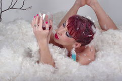 Beautiful model woman in feathers with red wine Royalty Free Stock Photography