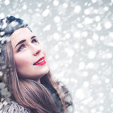 Beautiful Model Woman Looking Up on Snowfall Winter Background Royalty Free Stock Photography
