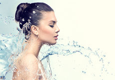 Beautiful model woman with splashes of water. In her hands Stock Photography