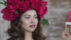 Beautiful model, with a wreath of scarlet peonies on his head. The model is photographed on the phone, a smartphone Royalty Free Stock Image