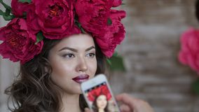 Beautiful model, with a wreath of scarlet peonies on his head. The model is photographed on the phone, a smartphone Stock Photo