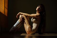 Beautiful modern ballet dancer with perfect body sits on the floor in the studio hall. Brunette long hair, flesh bodysuit color. concept of harmony and royalty free stock photography