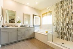 Beautiful Modern Custom Master Bathroom. With Vanity Mirrors and Cabinets royalty free stock image