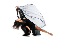 Beautiful modern dancer girl. Beautiful modern dancer young woman in black flyings fabrics making dance moves. Isolated on white background. Copy space stock photo