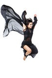 Beautiful modern dancer girl. Beautiful modern dancer young woman in black flyings fabrics making dance moves. Isolated on white background. Copy space stock image