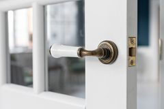 Beautiful modern door knob. Open, wooden front door from the interior of an upscale home with windows. Stock Photography