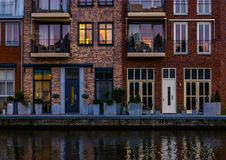 Beautiful modern dutch city architecture at night, terraced houses at the canal with balconies, Alphen aan den Rijn, The stock photos