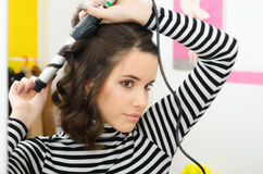 Beautiful modern girl curling her hair in front of the mirror Royalty Free Stock Photography
