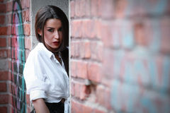 Beautiful modern girl near the brickwall. Senzual style. Fashion shot. Stock Image