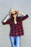 Beautiful modern girl near the wall. Youth style. Fashion shot. Red shirt and vellow hat with sunglasess Stock Image