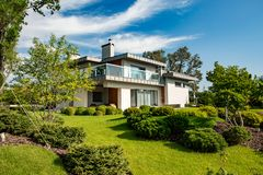 Beautiful modern house in cement, view from the garden. Loft stock photo