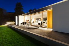Beautiful modern house in cement. View from the garden, night scene Stock Photo