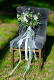Beautiful modern lush bridal bouquet is standing. On a chair in the forest Royalty Free Stock Image