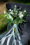 Beautiful modern lush bridal bouquet is standing. On a chair in the forest Royalty Free Stock Images