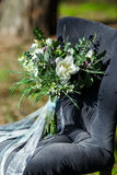 Beautiful modern lush bridal bouquet is standing. On a chair in the forest Stock Photos