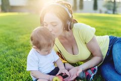 Beautiful modern mom playing in a green meadow with her cute baby son in a Sunny Park. Concept of the joy of motherhood. Beautiful young modern mom playing in a royalty free stock photos