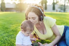 Beautiful modern mom playing in a green meadow with her cute baby son in a Sunny Park. Concept of the joy of motherhood. Beautiful young modern mom playing in a royalty free stock photography