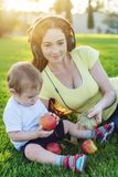 Beautiful modern mom playing in a green meadow with her cute baby son in a Sunny Park. Concept of the joy of motherhood. Beautiful young modern mom playing in a stock photography