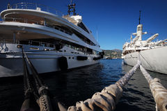 Beautiful modern ships at moorage. Photo closeup of beautiful modern white ships sea liners yachts vessels at moorage with nautical ropes at seashore clear water Stock Image