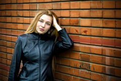 Beautiful modern woman in front of brick wall. Beautiful blond girl standing in front of old brick wall Stock Images
