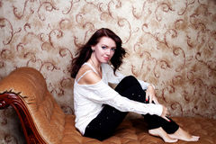 Beautiful modern woman sitting on vintage couch Royalty Free Stock Photos
