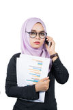 Beautiful modern Young Asian Muslim business woman holding a cellphone and reports Royalty Free Stock Photo