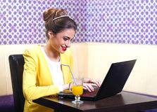 Beautiful modern young woman sitting at the laptop. In cafe Royalty Free Stock Image