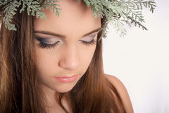 Beautiful modest young girl with bright makeup, smoky eyes on new year`s wreath from the Christmas tree and cones royalty free stock photo